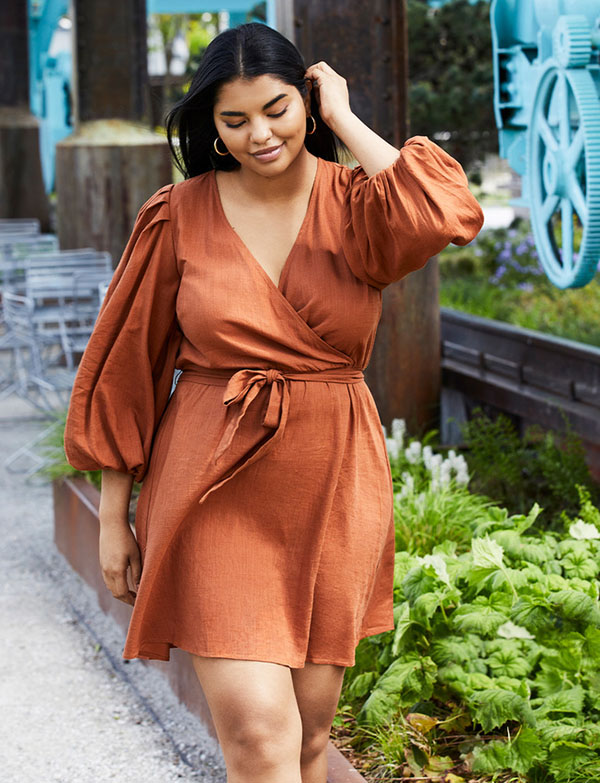 A plus-size model wearing a rust wrap mini dress.