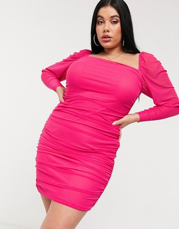 A plus-size model wearing a hot pink ruched mini dress.