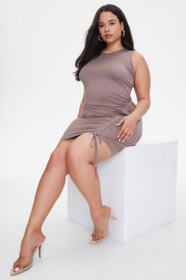 A plus-size model wearing a taupe ruched mini dress.