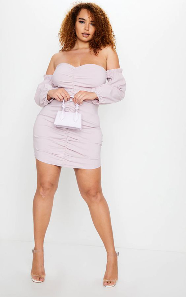 A plus-size model wearing a lavender ruched mini dress.