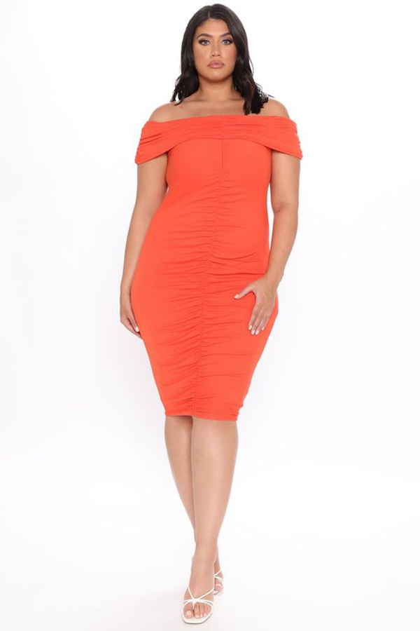 A plus-size model wearing an orange ruched midi dress.
