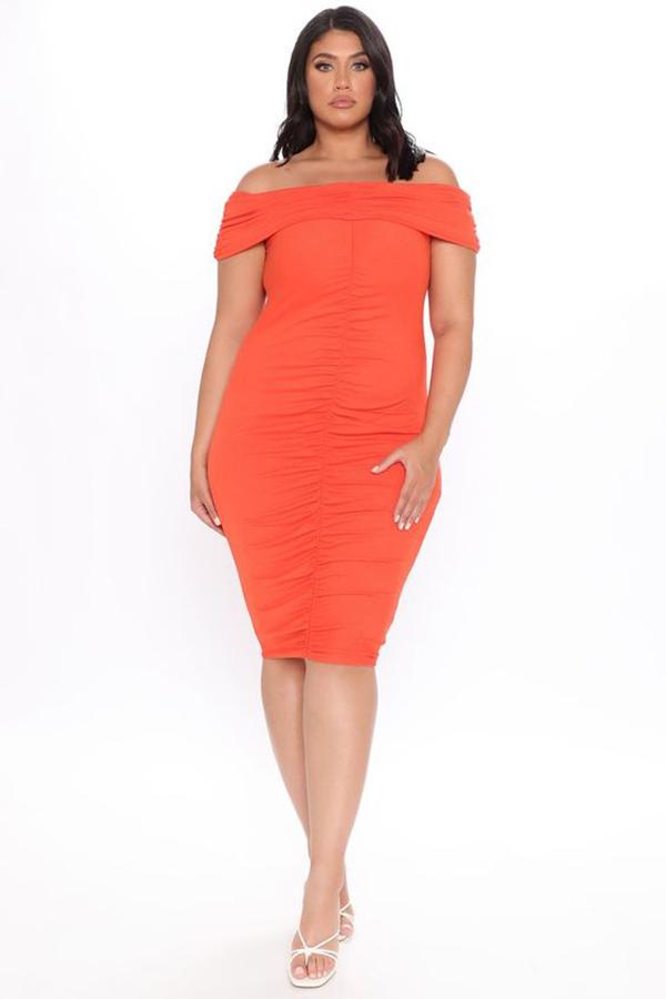 A plus-size model wearing an orange ruched midi dress.