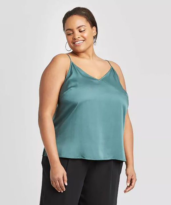 A plus-size model wearing a light blue satin cami.
