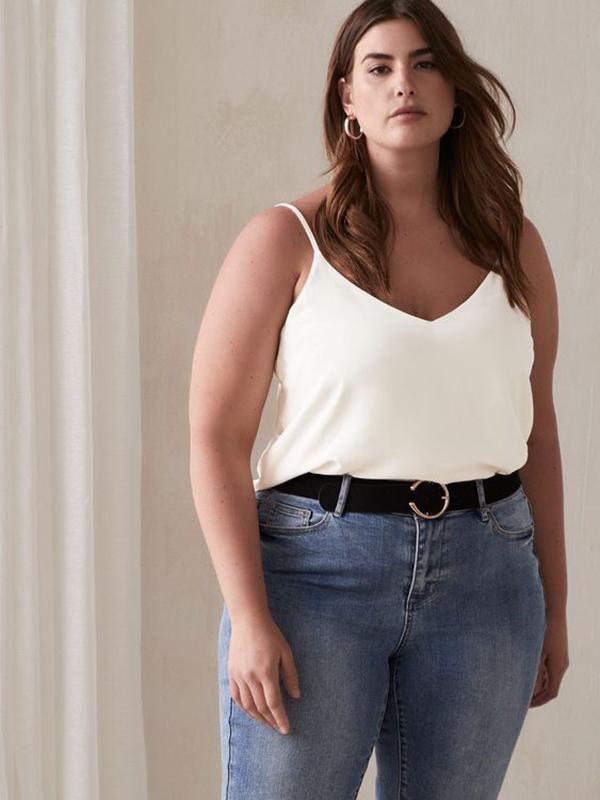A plus-size model wearing a white satin cami.