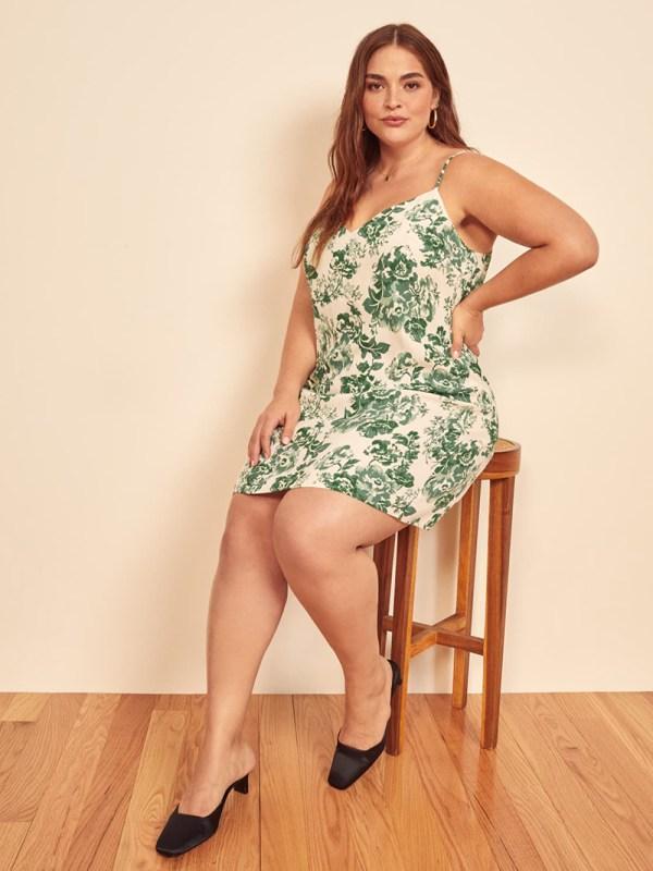 A plus-size model wearing a green printed mini slip dress.