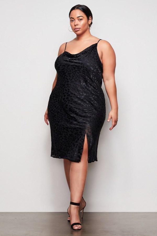 A plus-size model wearing a black slip dress.