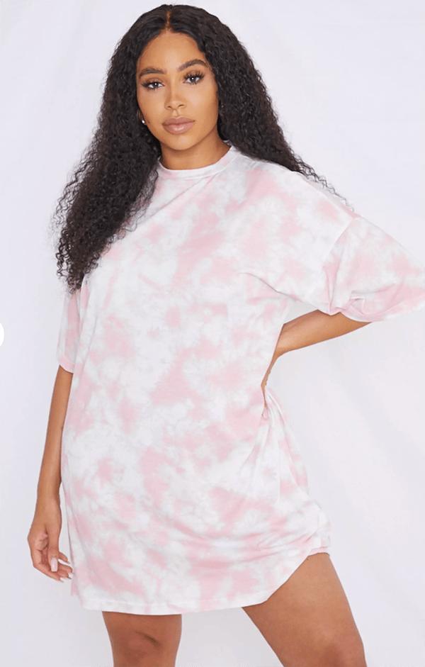 A plus-size model wearing a pink tie-dye T-shirt dress.