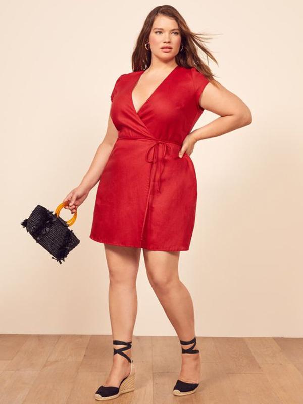 A plus-side model wearing a red wrap mini dress.