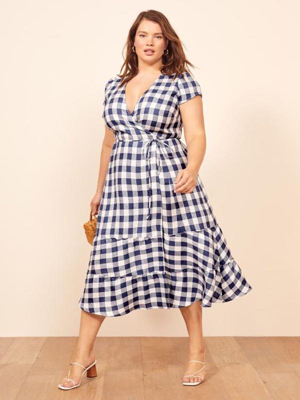 A plus-side model wearing a gingham wrap dress.
