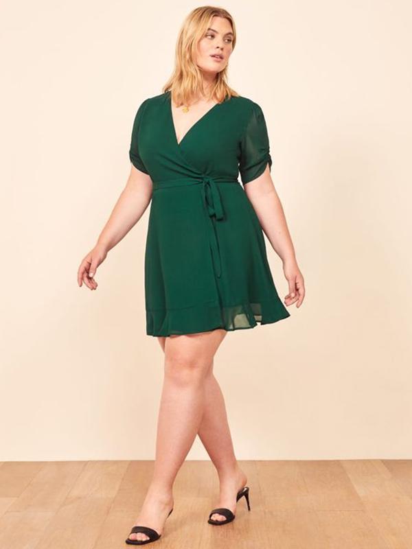 A plus-side model wearing an emerald green wrap dress.