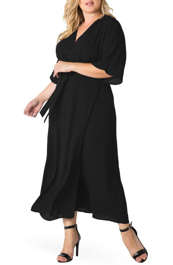 A plus-side model wearing a black wrap dress.