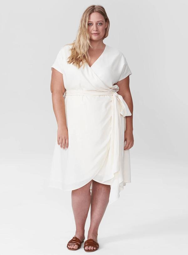 A plus-side model wearing a white wrap dress.