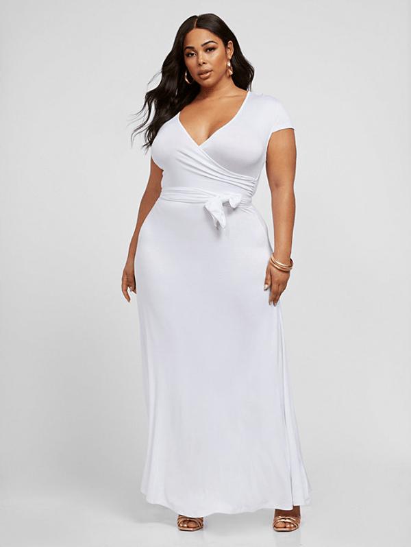 A plus-side model wearing a white wrap maxi dress.