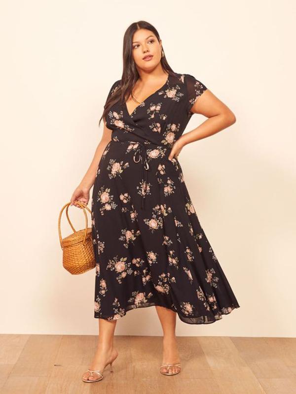A plus-side model wearing a black floral wrap dress.