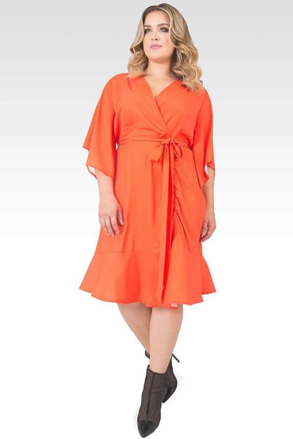 A plus-side model wearing a red-orange wrap dress.