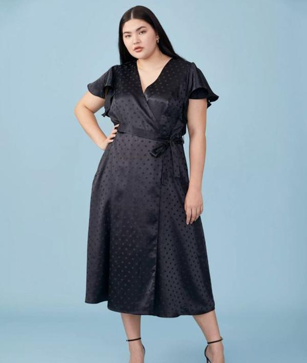 A plus-side model wearing a black satin wrap dress.