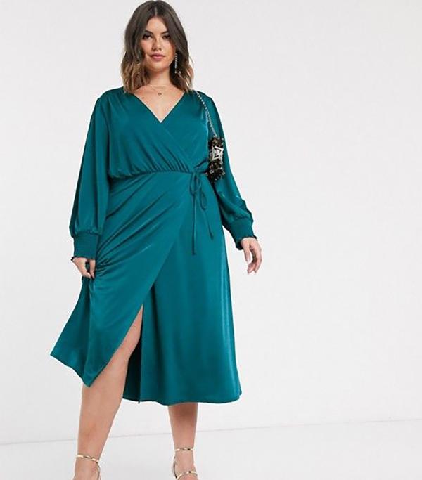 A plus-side model wearing a teal satin wrap dress.