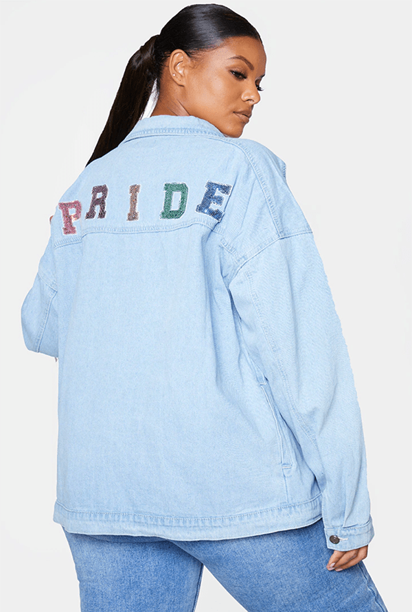 "A plus-size model wearing a denim jacket with the word ""pride"" emblazoned on the back."