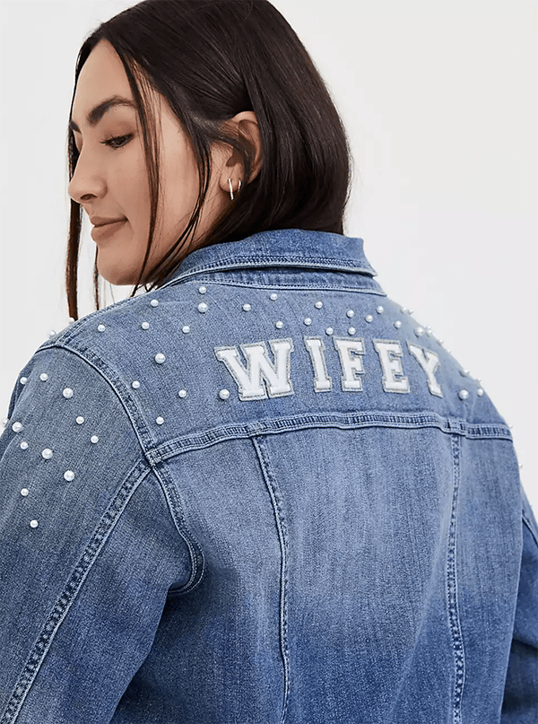 "A plus-size model wearing a denim jacket adorned with pearls and the word ""wifey."""