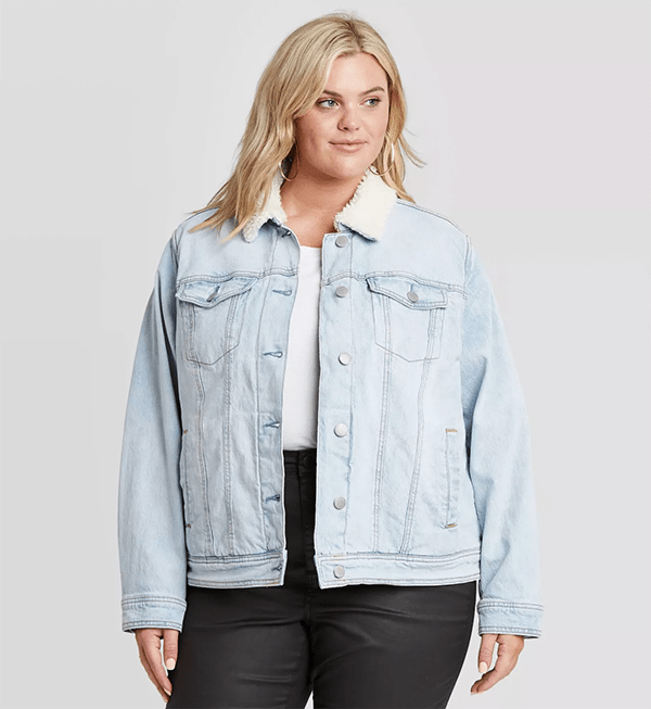 A plus-size model wearing a fur-lined denim jacket.