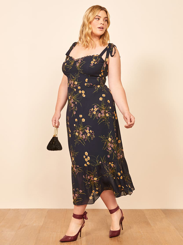 A plus-size model wearing a floral fall maxi dress.