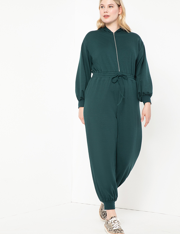 A plus-size model wearing a dark green lounge jumpsuit.