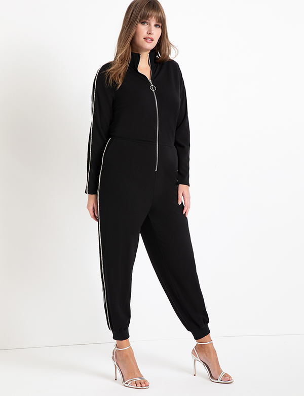 A plus-size model wearing a black zip-up lounge jumpsuit.