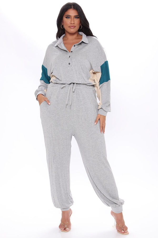A plus-size model wearing a gray colorblock lounge jumpsuit.