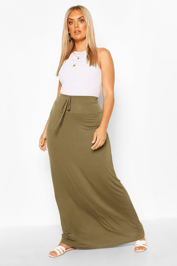 A plus-size model wearing an olive green maxi skirt.