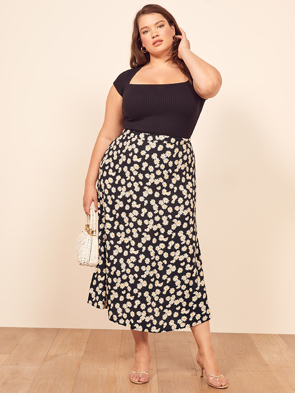 A plus-size model wearing a floral maxi skirt.