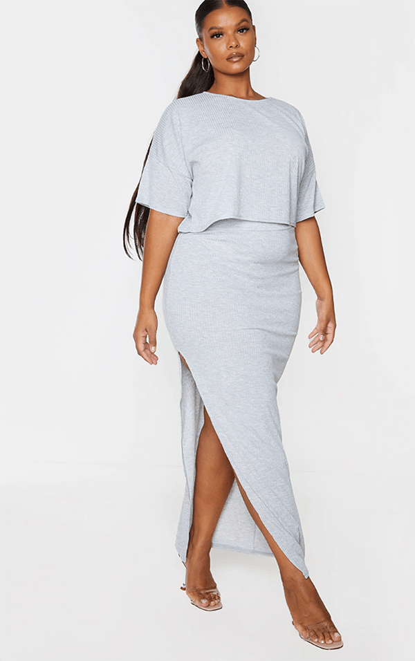 A plus-size model wearing a gray maxi skirt.