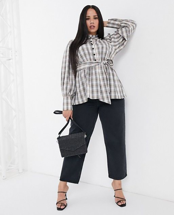 A plus-size model wearing a plaid blouse.