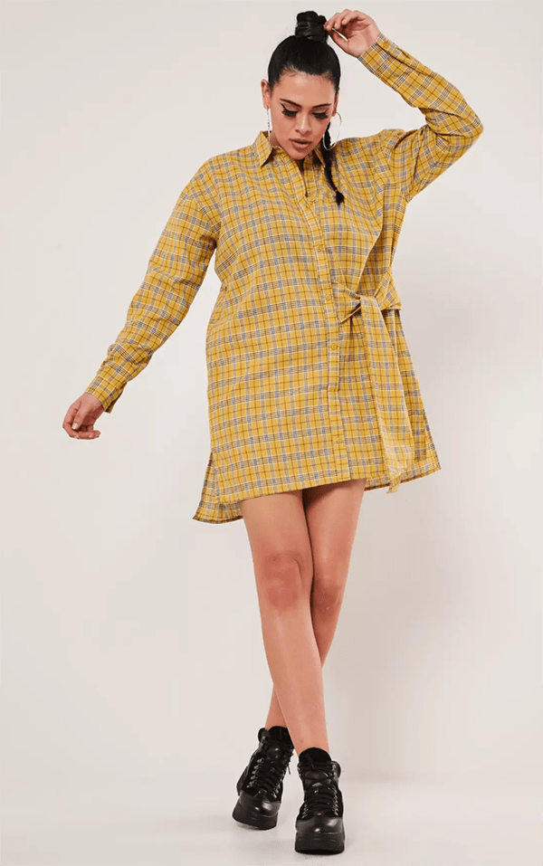 A plus-size model wearing a plaid shirtdress.
