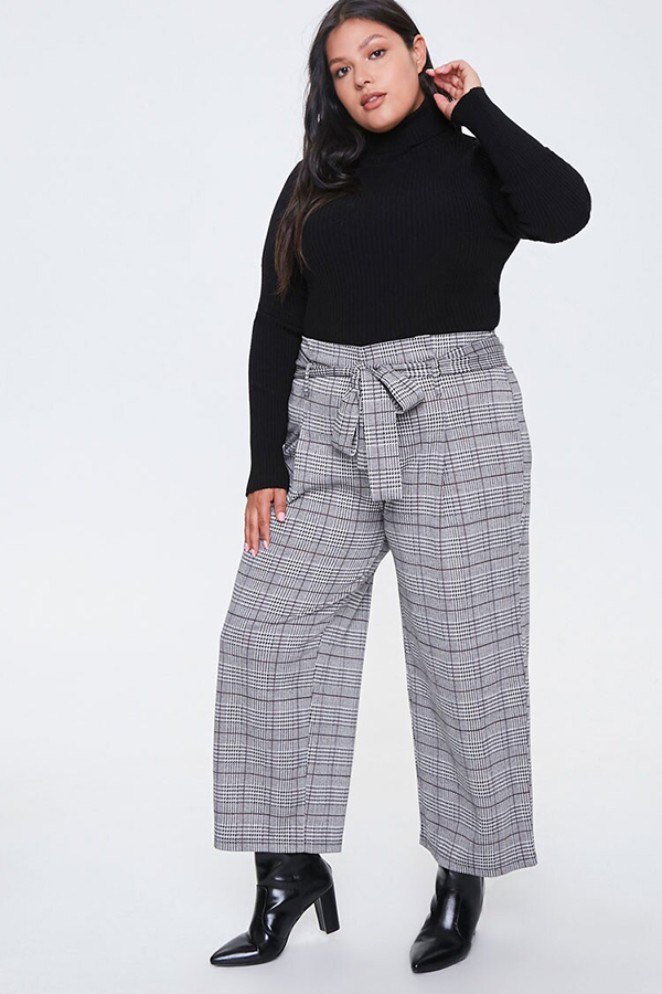 A plus-size model wearing a pair of plaid pants.