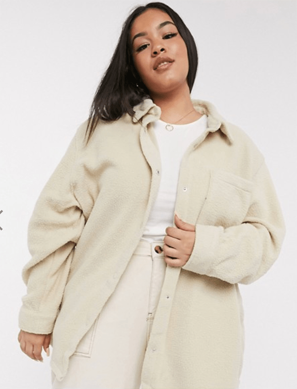 A plus-size model wearing a white fuzzy shacket.