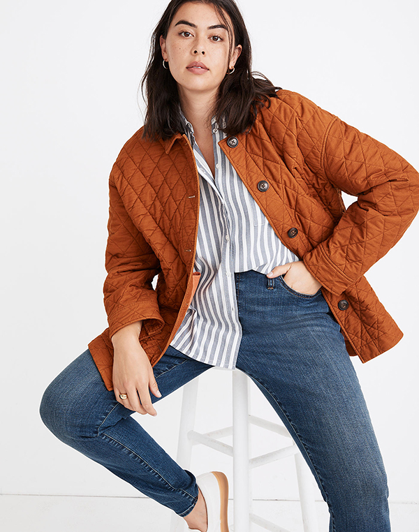 A plus-size model wearing a rust quilted shacket.