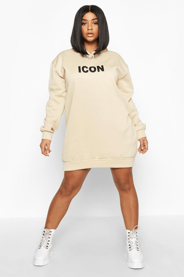 """A plus-size model wearing a beige sweatshirt dress with the word """"icon"""" emblazoned on it."""