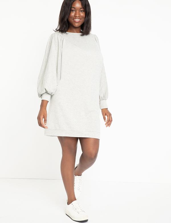 A plus-size model wearing a light gray sweatshirt dress.