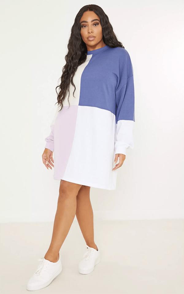 A plus-size model wearing a colorblock sweatshirt dress.