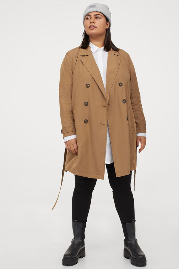 A plus-size model wearing a tan trench coat.