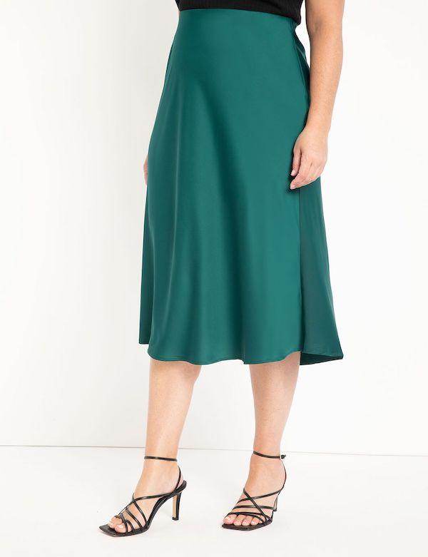 A model wearing a plus-size satin skirt.