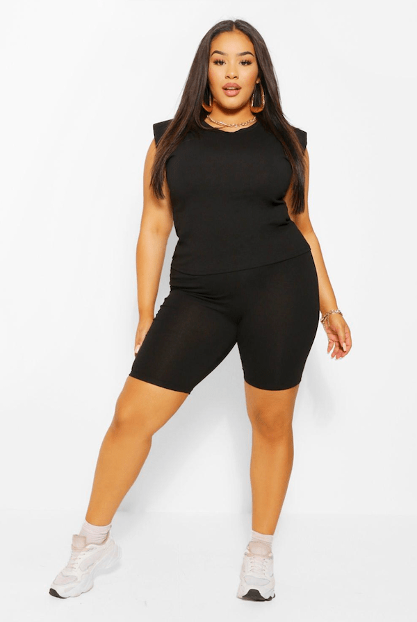 A plus-size model wearing a black plus-size muscle tee and shorts set.