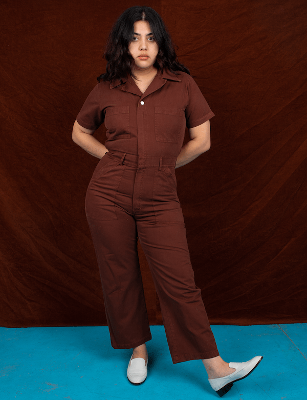 A model wearing a plus-size utility jumpsuit in brown.