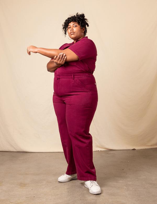 A model wearing a plus-size utility jumpsuit in plum.