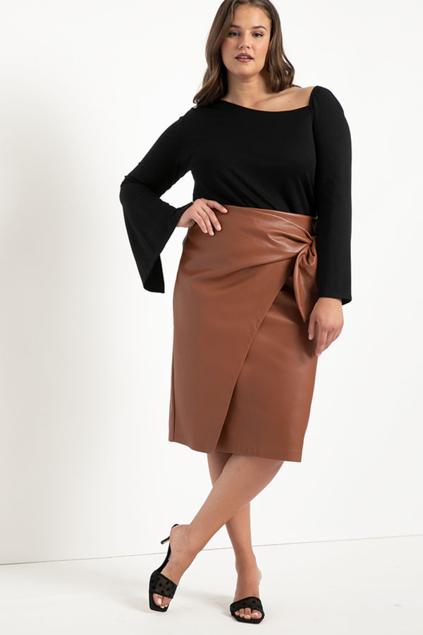 A plus-size model wearing a brown wrap leather midi skirt.