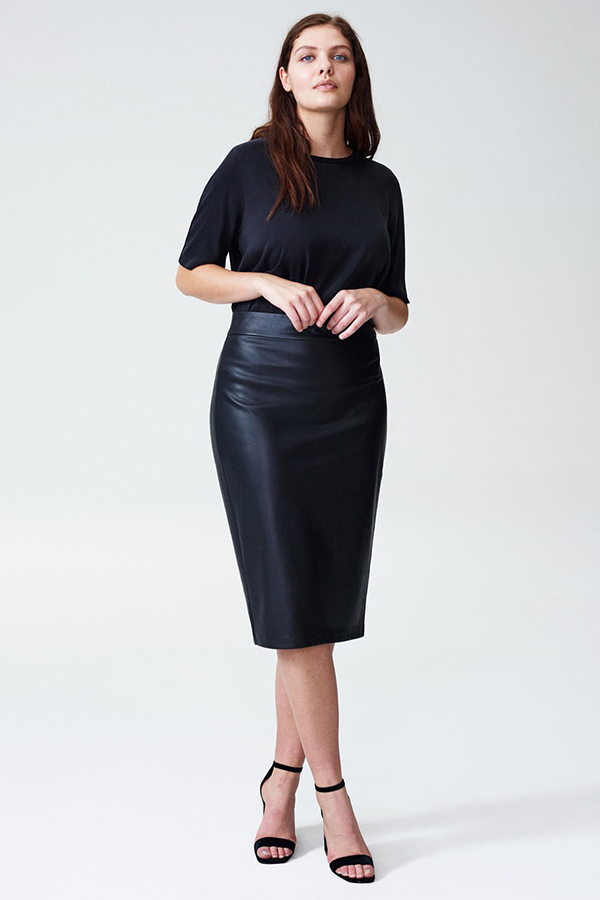 A plus-size model wearing a black leather midi skirt.