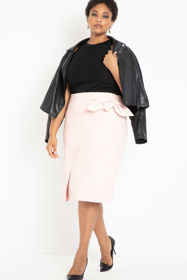 A plus-size model wearing a light pink leather midi skirt.