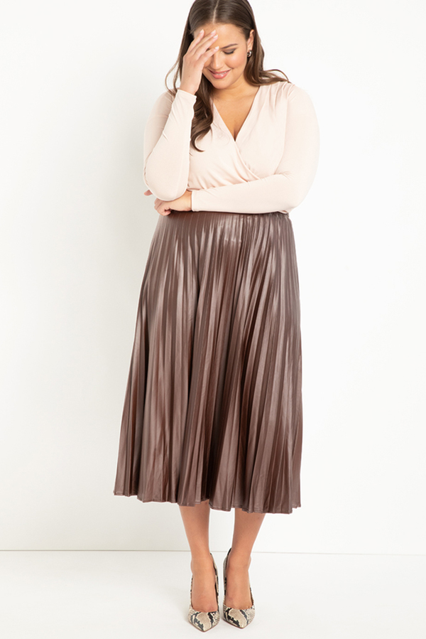 A plus-size model wearing a brown pleated leather midi skirt.