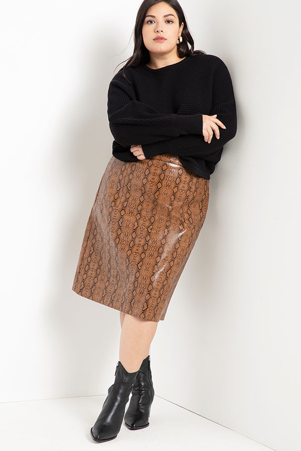 A plus-size model wearing a brown leather midi skirt.