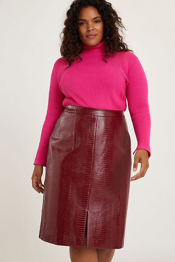 A plus-size model wearing a red leather midi skirt.